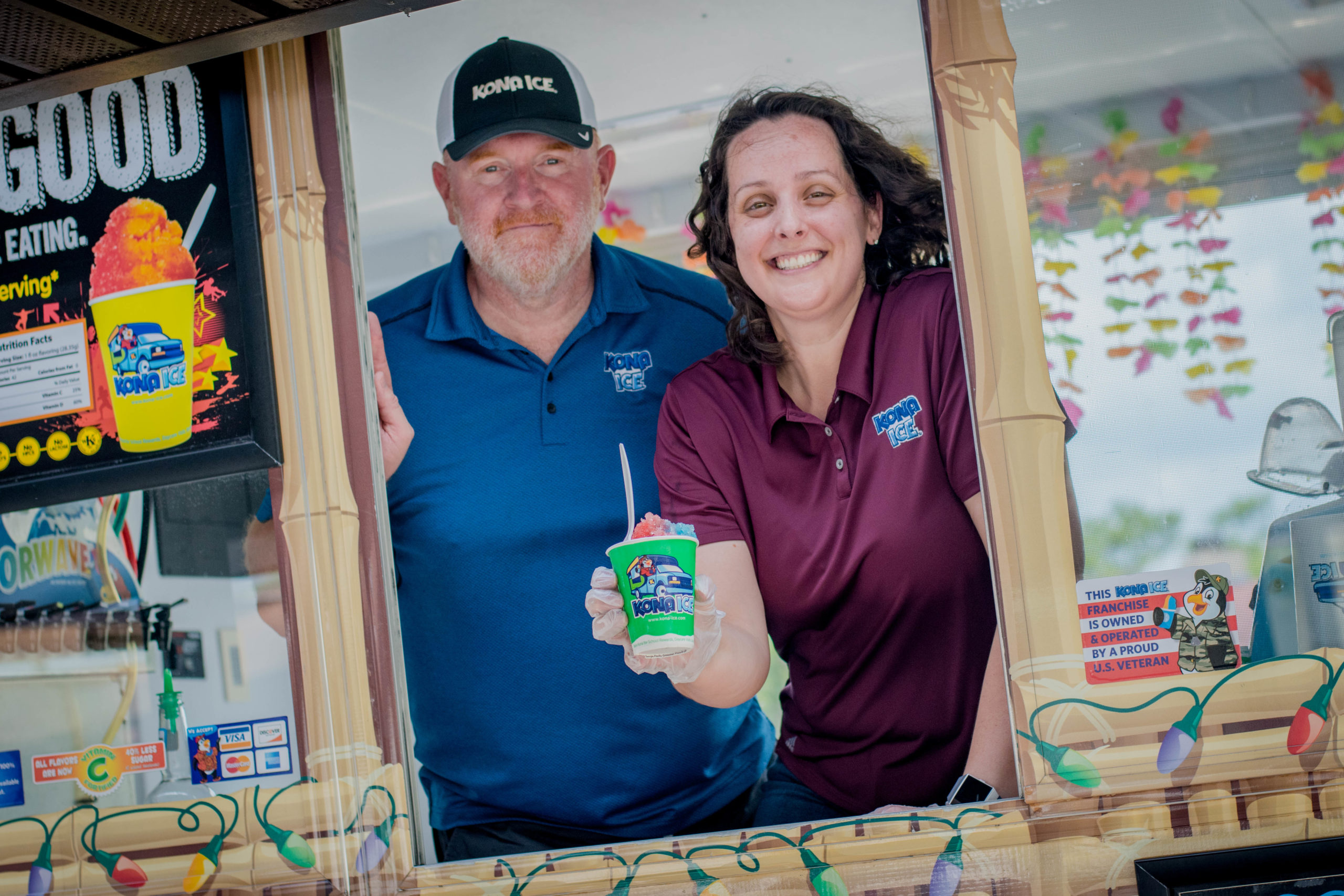 Slagle and Minton pictured in the window of the Kona Ice truck.