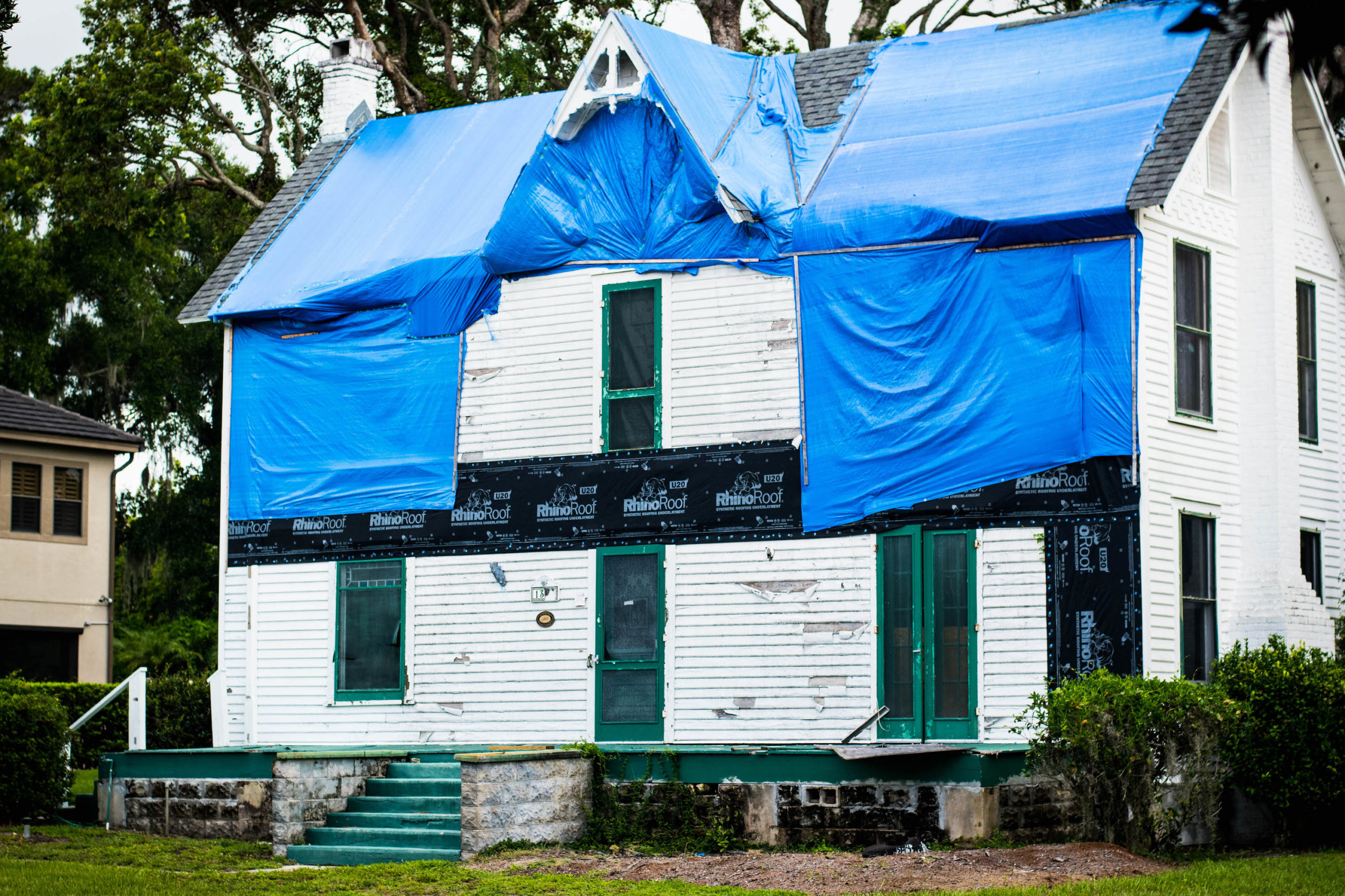 Front facing view of the Waddell House covered in blue tarps.