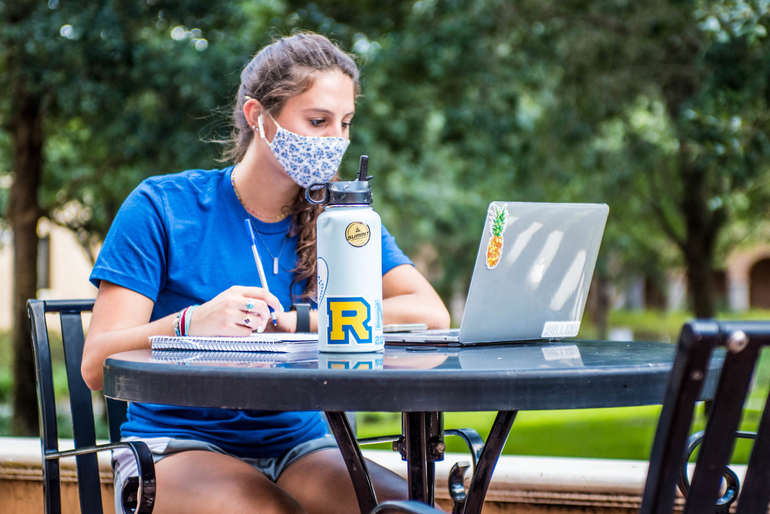 Rollins College student studies outside while wearing a face mask.
