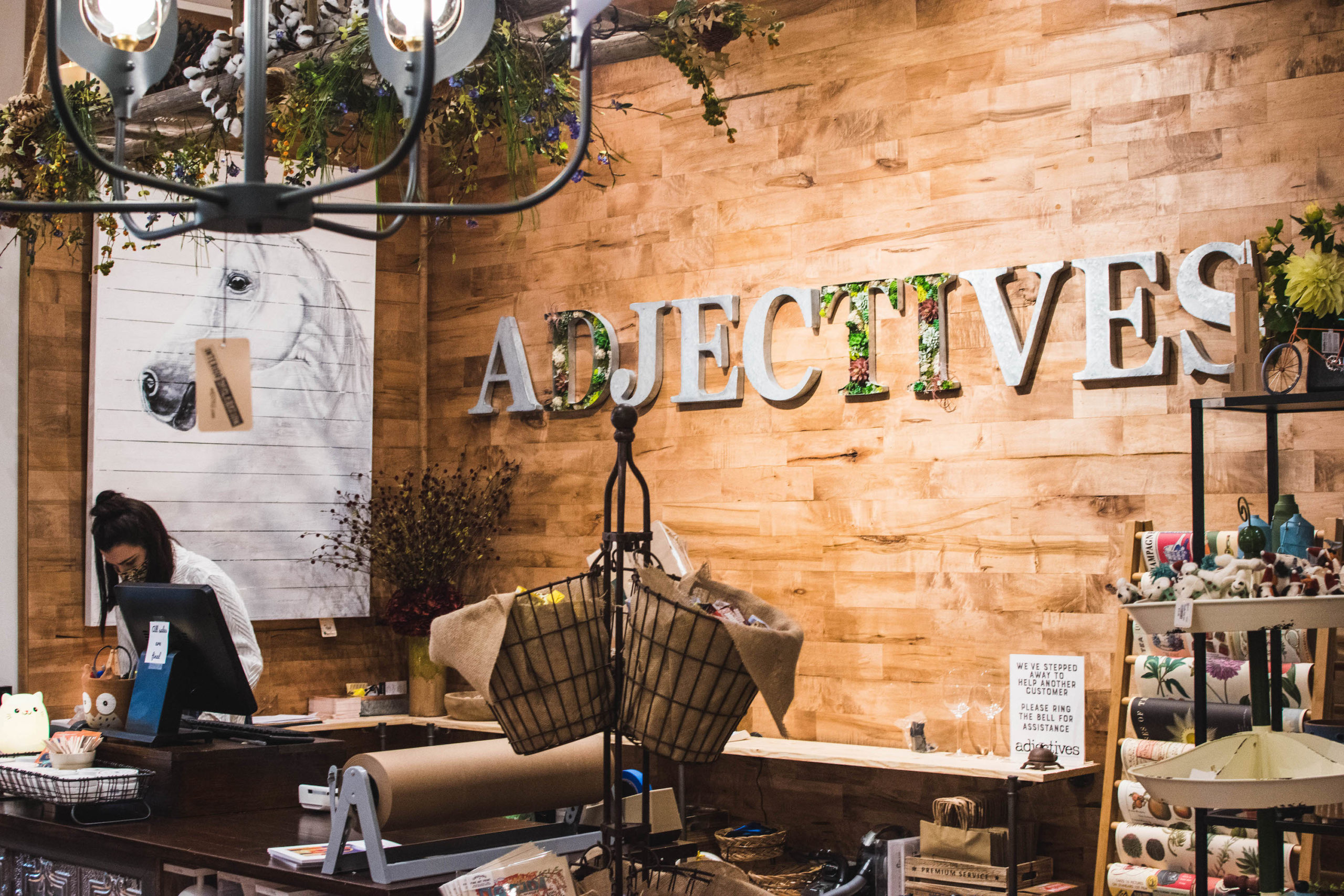 Adjectives spelled out in large metal letters on the wall behind the cashier area at Adjectives Market on Park Avenue.
