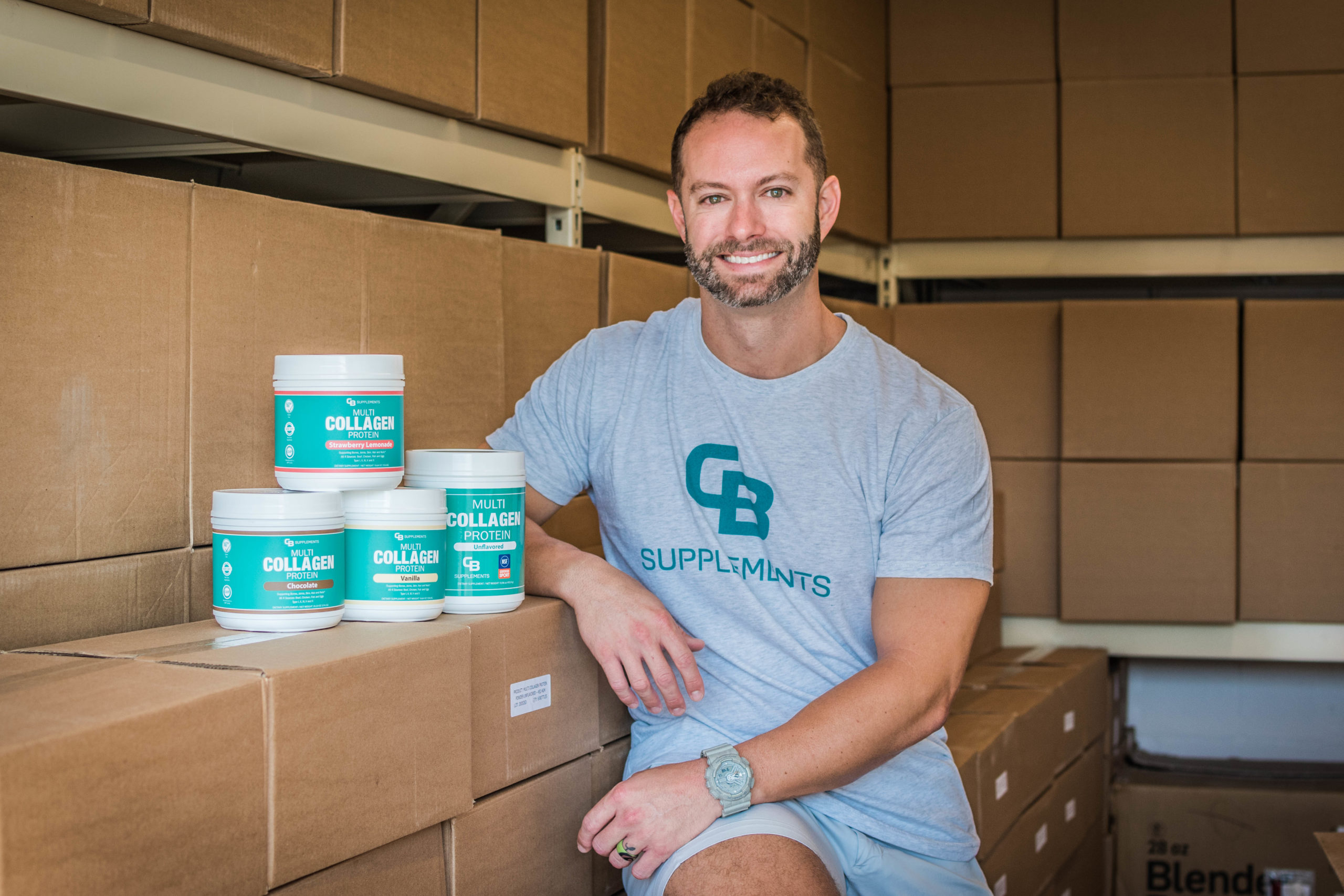 Charlie Bailes sits on stacked boxes with his product.