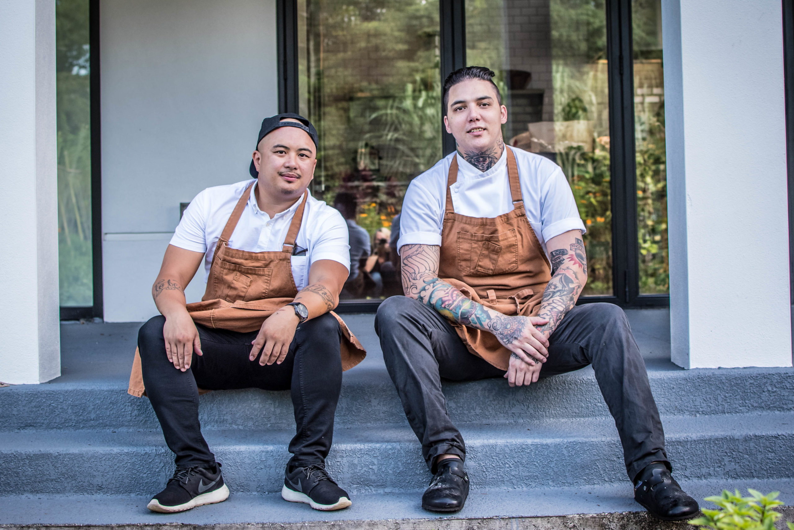 Chef Collantes and Chef Cha sit on steps outdoors in their aprons.