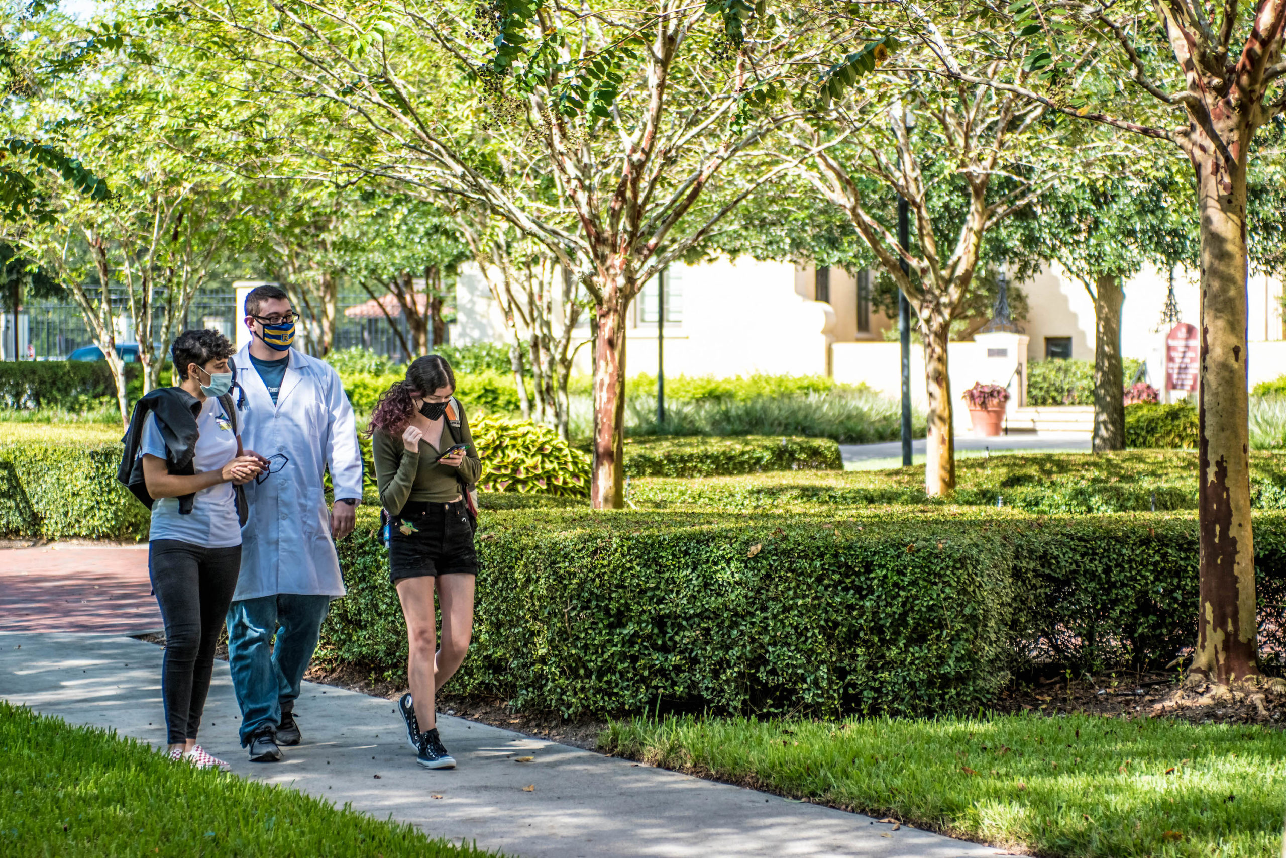 Students at Rollins College walk outdoors with face masks on.