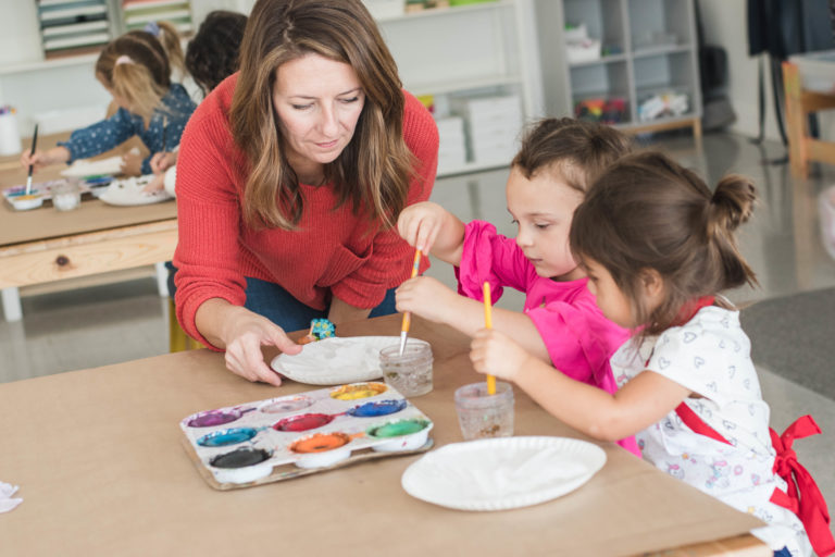 Woman shows young girls how to paint.