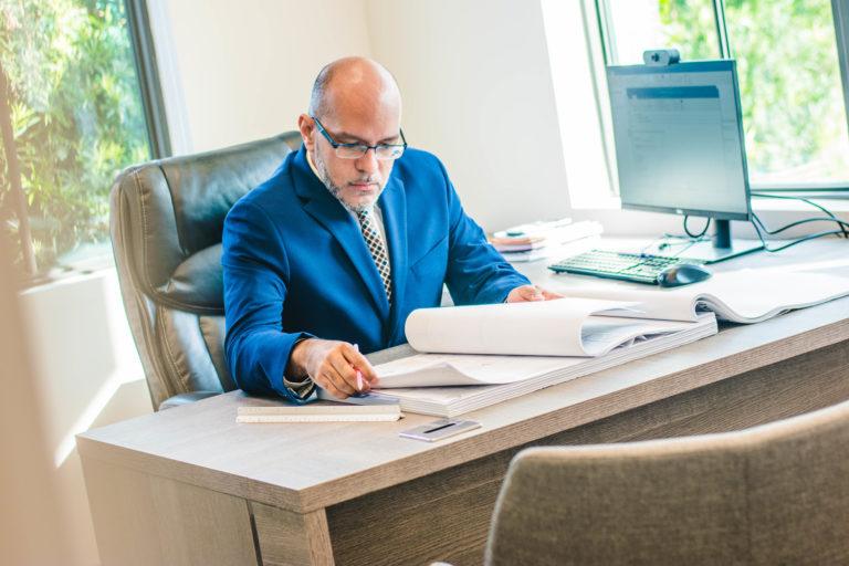 Manuel Velazquez sitting at his desk reviewing blueprints.
