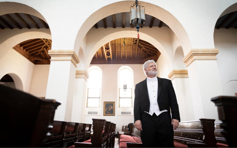 Dr. John V. Sinclair stands in between the pews of Knowles Chapel.