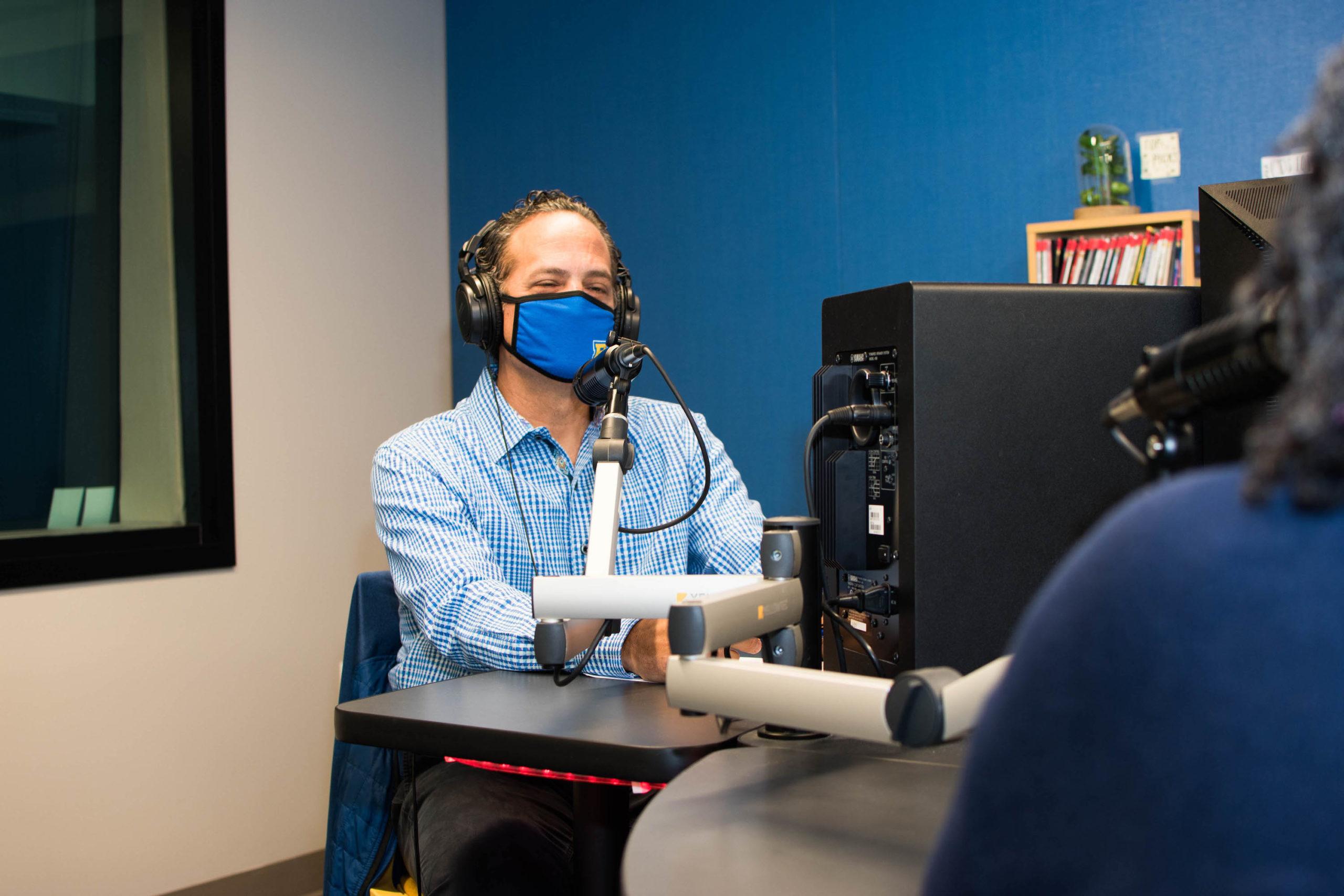 Sam Stark conducts podcast in recording studio.