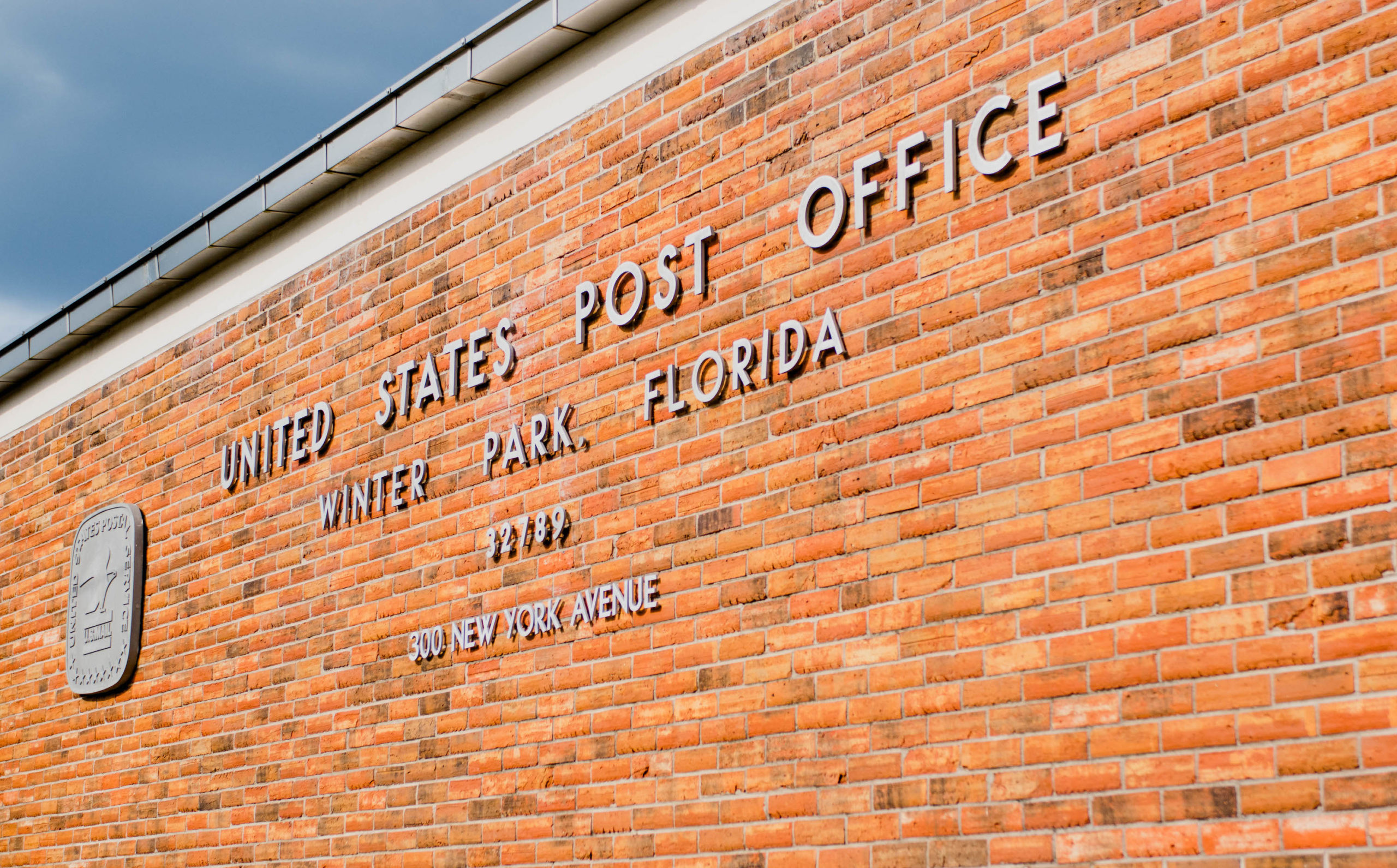 Winter Park Post Office signage on brick wall of building.