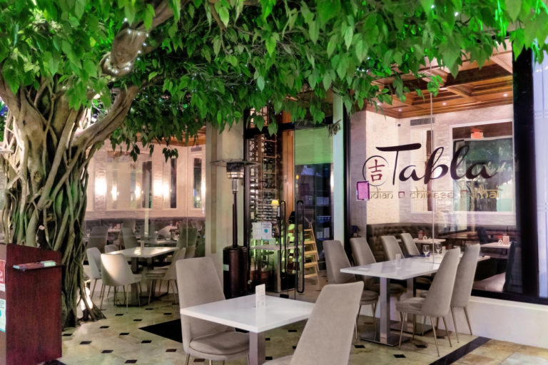 The front of Tabla restaurant shows a live tree hovering above the entrance door, along with tables outside.