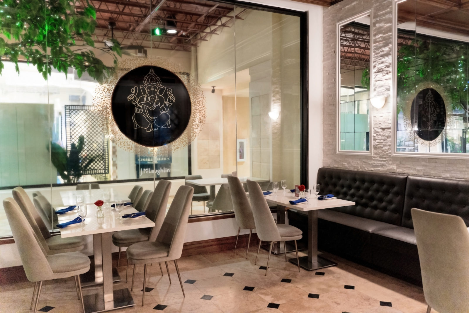 Inside dining area at Table with neutral chairs, white tables, tiled floors, and a leather booth against the wall.