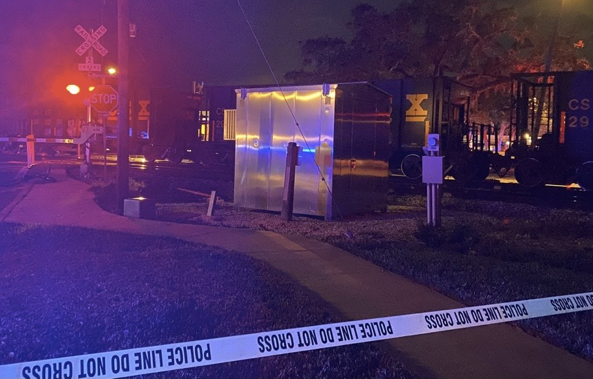 Crime scene tape blocks locals from entering the scene in front of the train tracks with red railroad crossing lights.