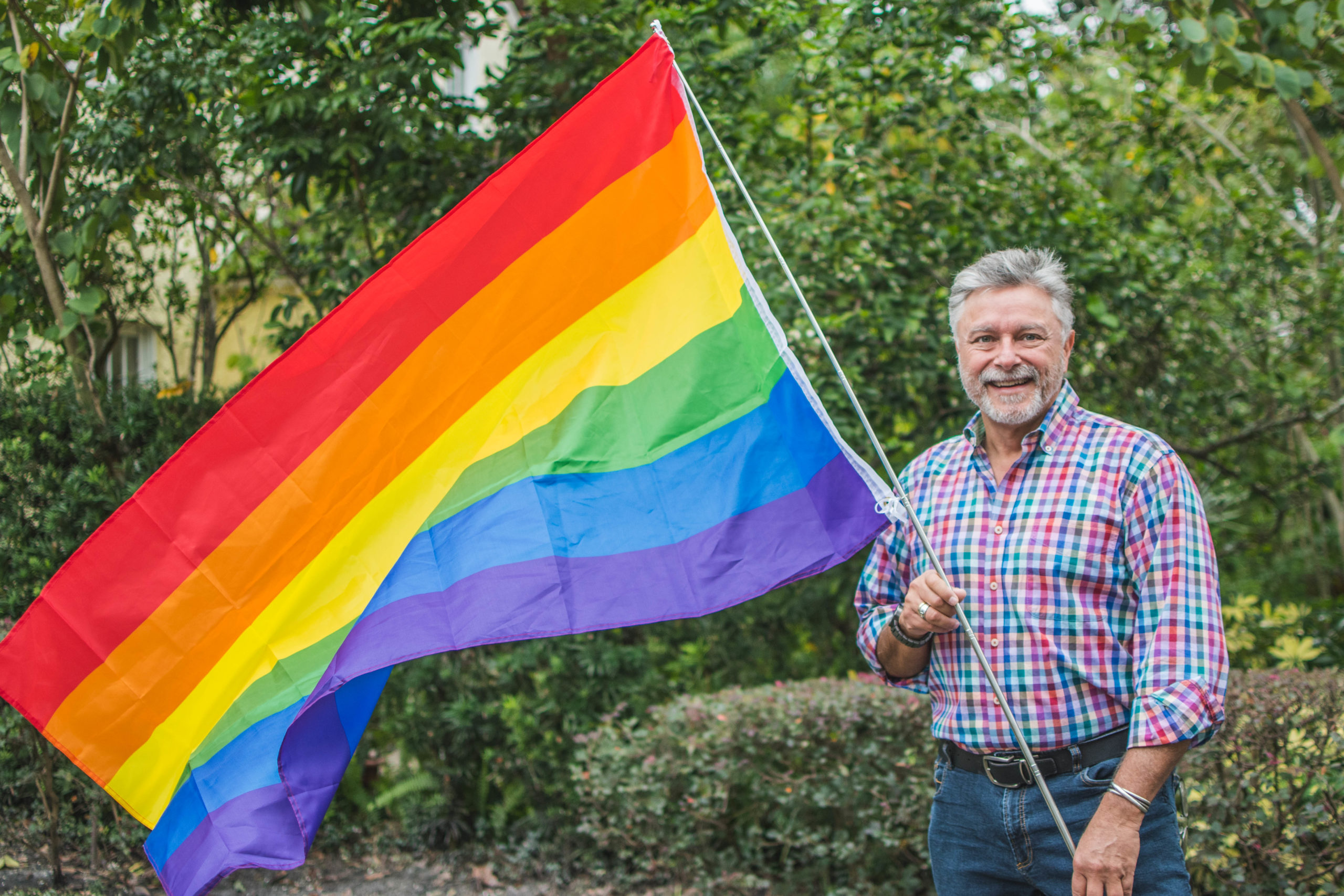 Thor Falk holds up a rainbow LGBTQ pride flag.