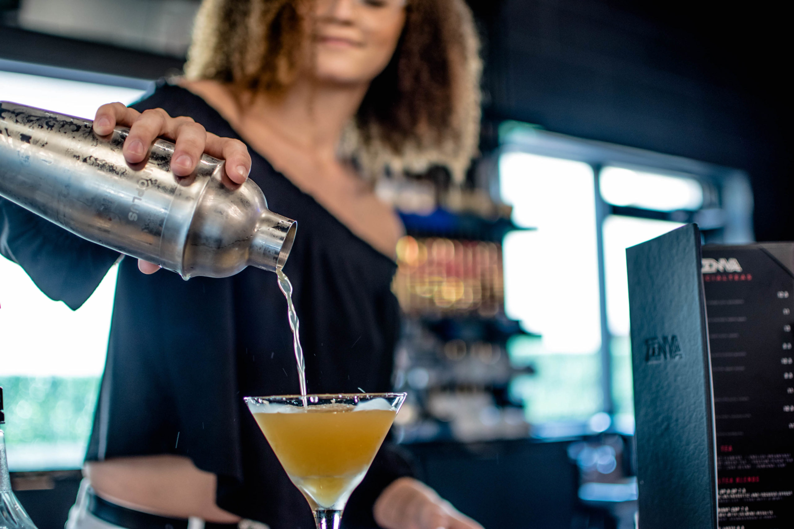 Woman pours a drink into a martini glass behind a bar.