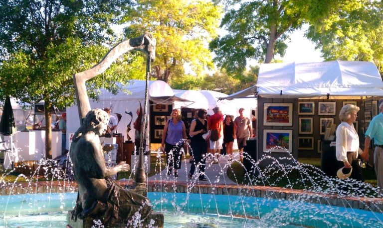 The Sidewalk Art Festival last year shows patrons shopping near a fountain and statue.