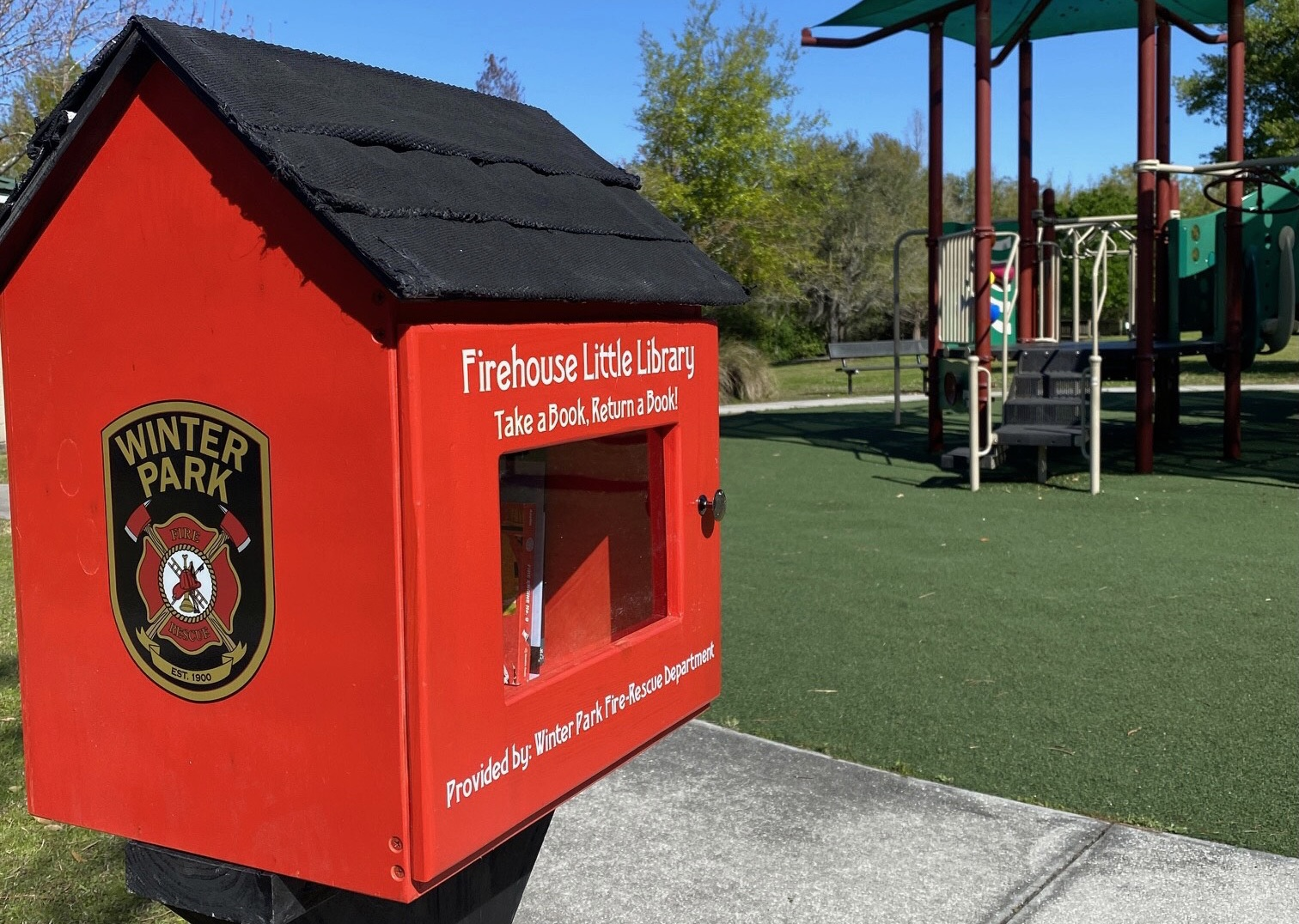 A red little library shows the Winter Park Fire-Rescue Department badge and there is a playground in the background.