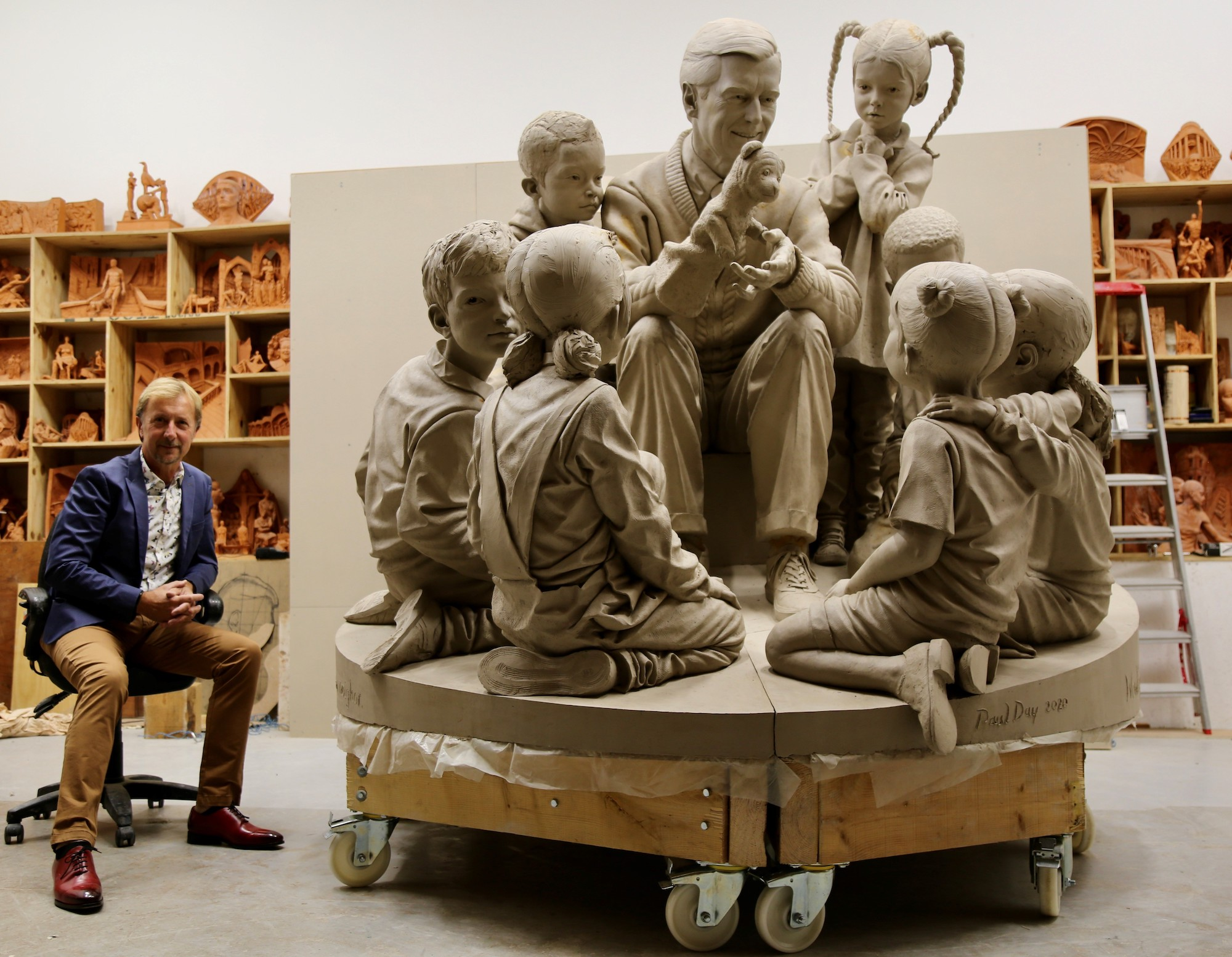 "Paul day sits next to ""A Beautiful for a Neighbor"" statue featureing Mister Rogers, his puppets, and children."