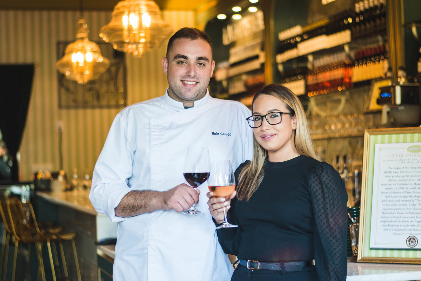 Chef Théo and Danielle Goupil cheers wine glasses in front of the Financier Bistro.