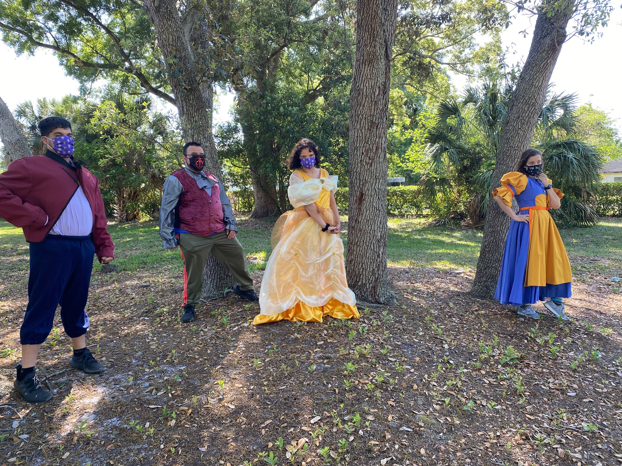 Image shows four actors dressed up as members of the Beauty and the Best cast standing outside in front of trees.