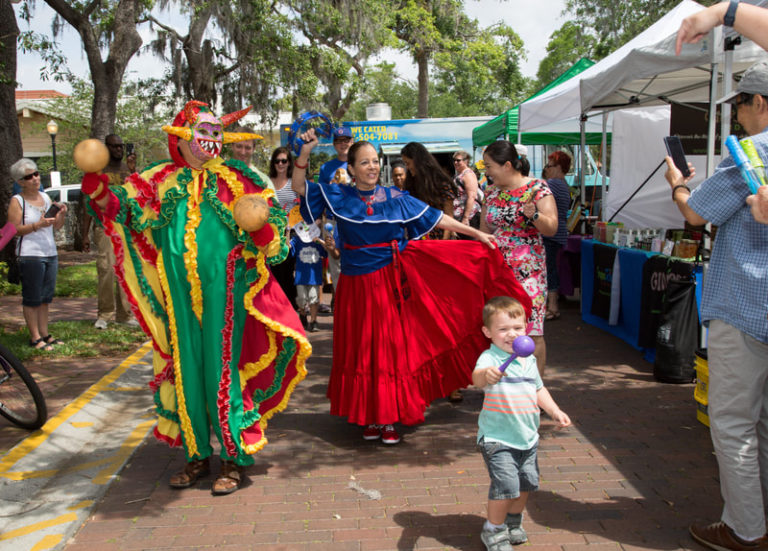 Performers in colorful, traditional clothing dance with patrons at the art festival.