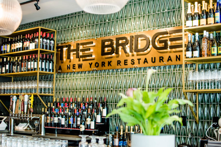 Sign that reads The Bridge above the bar of a restaurant.
