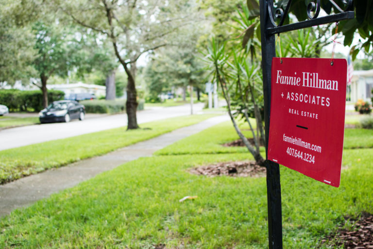 A red Fannie Hillman real estate sign posted in a front lawn.
