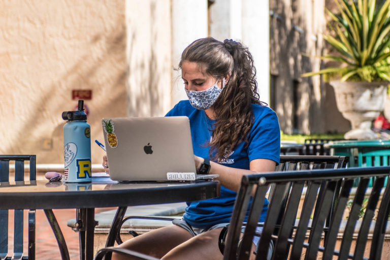 Rollins student sits masked outdoors on her laptop.