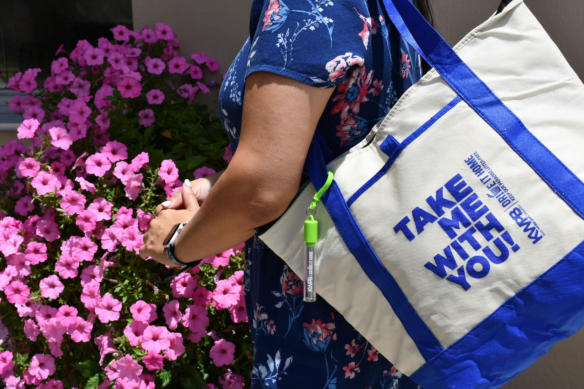 Woman holds large tote bag in front of a bush of flowers.