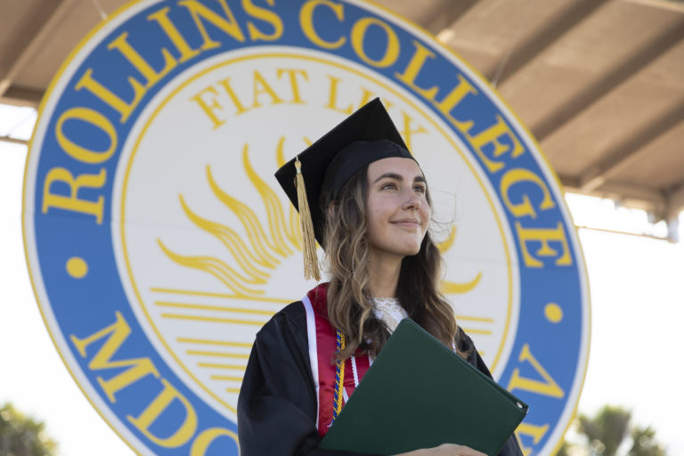 Photo shows graduate holding diploma in front of the Rollins College crest.
