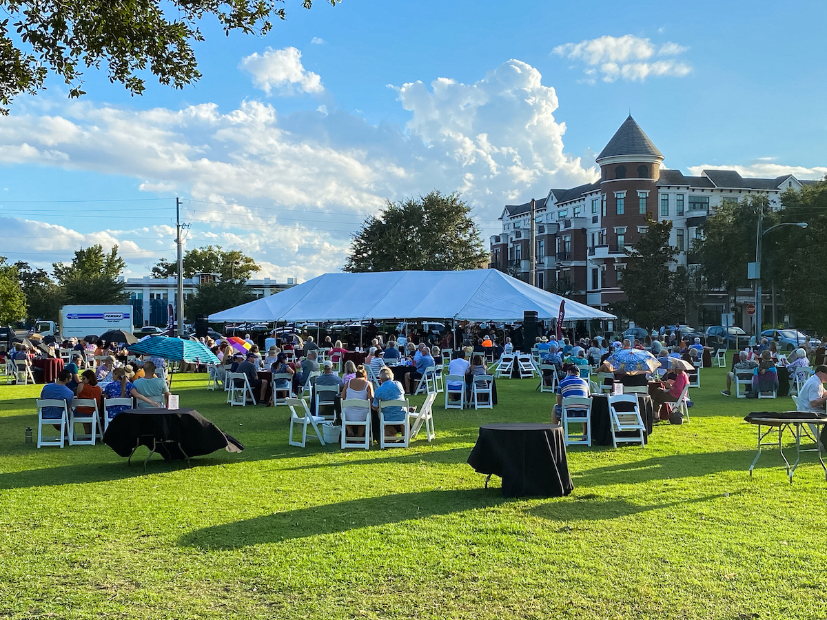 A white tent is shown on a green lawn and blue sky with people sitting at tables.