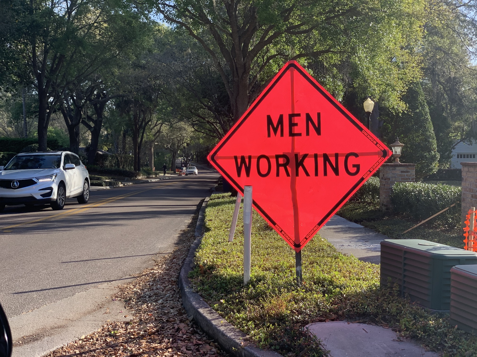 "A large, orange ""Men Working"" sign propped up on a sidewalk."