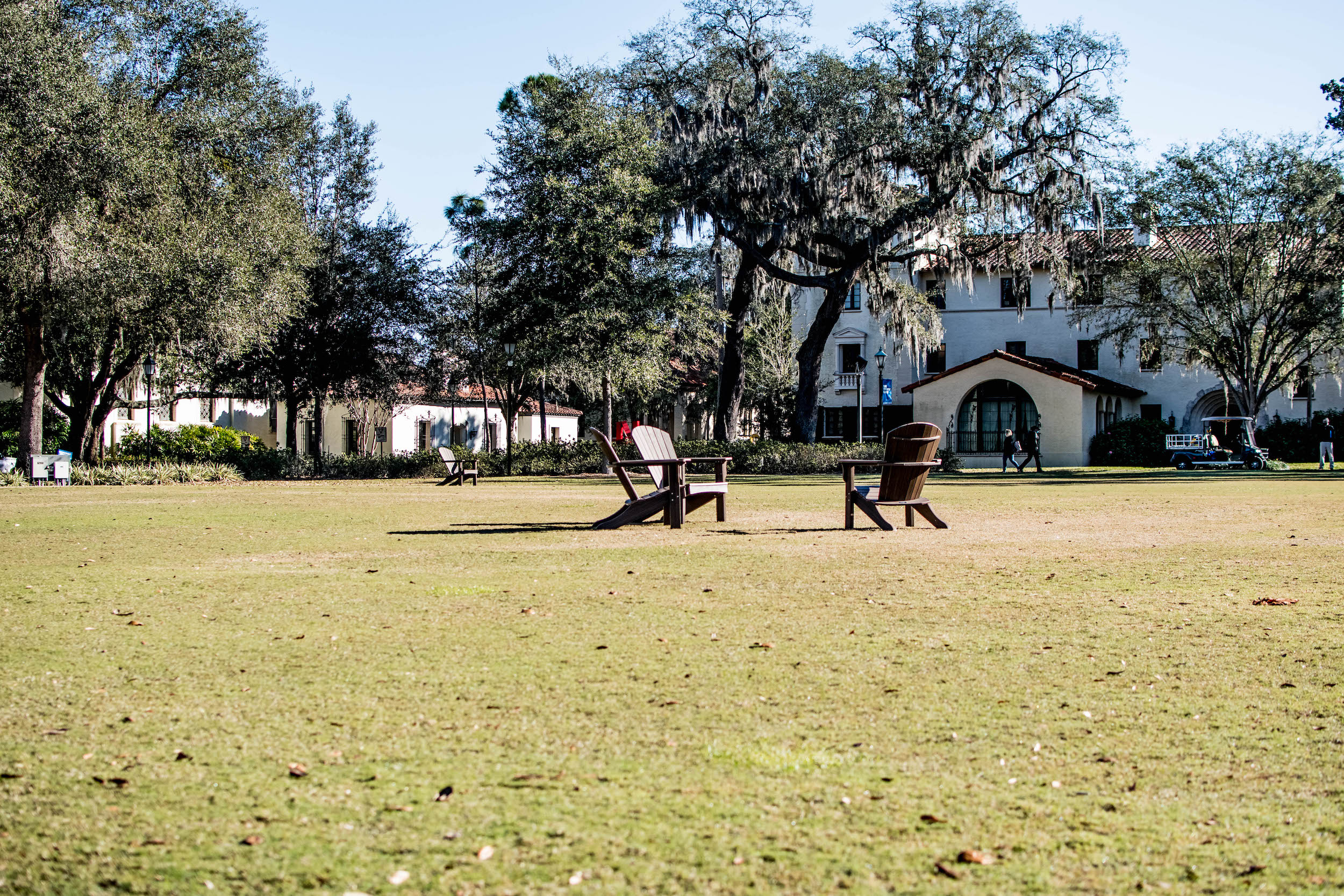 Photo pictures green space with chairs in front of the Rollins College campus.