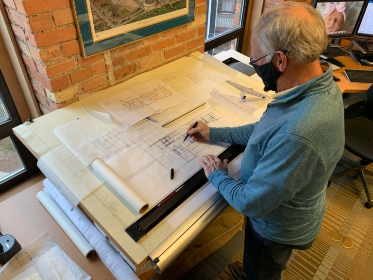 Image shows a man sketching plans on large architectural paper.