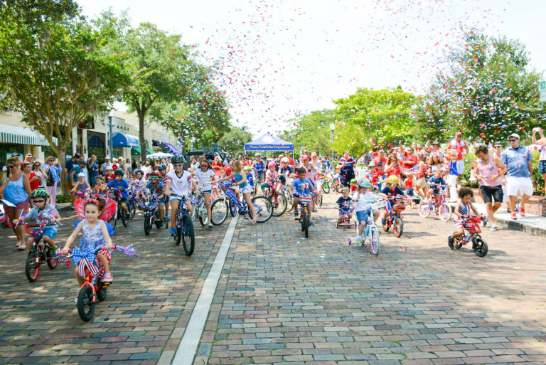 Many people riding bikes on a grey paved road celebrate the Fourth of July with red, white, and blue confetti.