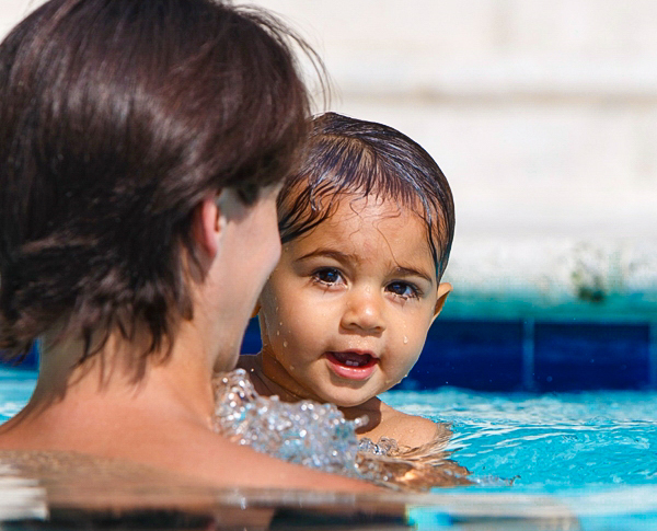 Baby swims in blue pool with teacher in the sunlight.