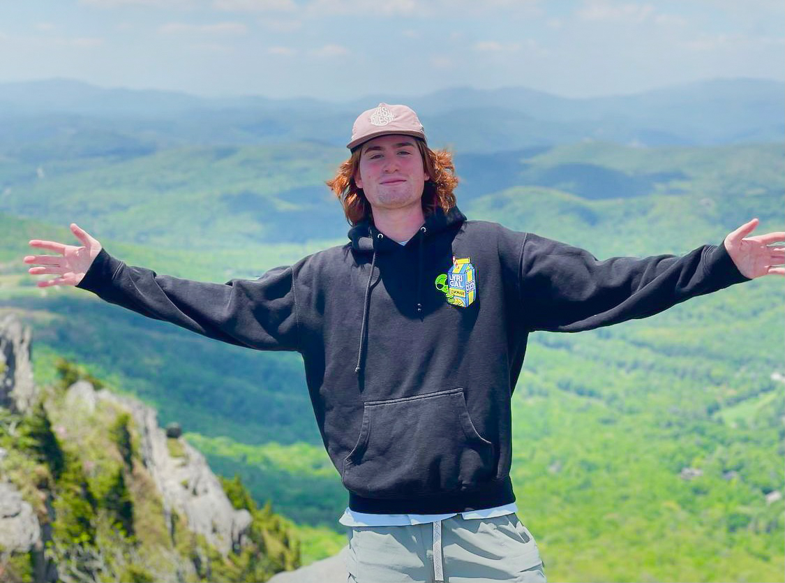 A tall boy with red hair stands on a mountain next to a green park.