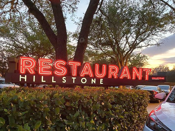 Red Hillstone sign lit up and hovering over a green bush