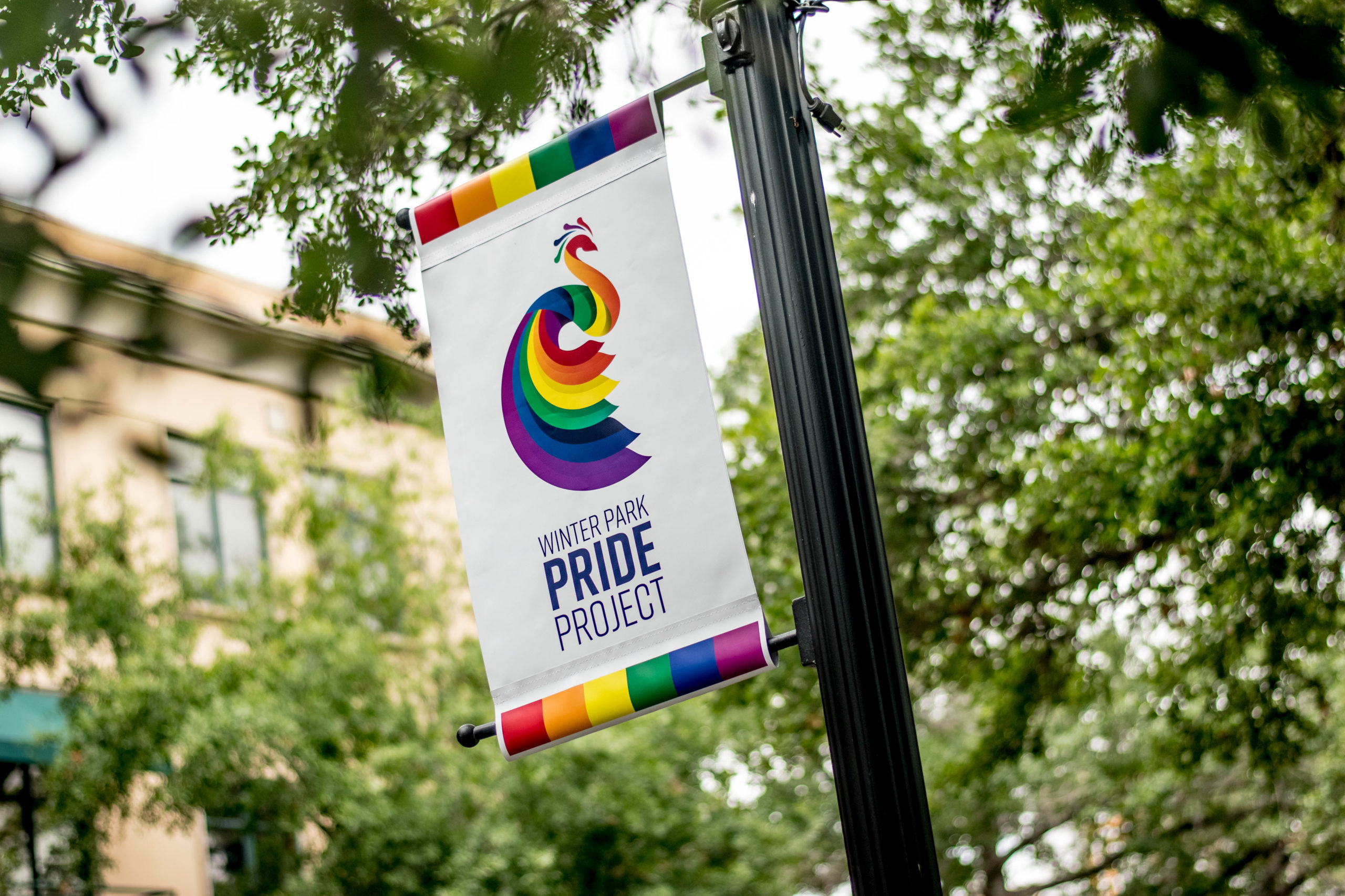 A flag pole shows a Winter Park Pride flag hanging with rainbows in front of green trees.