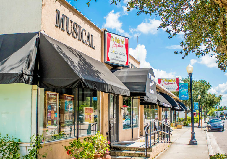 Image shows beige building with black awning and sign that says musicals with a blue sky and green bushes
