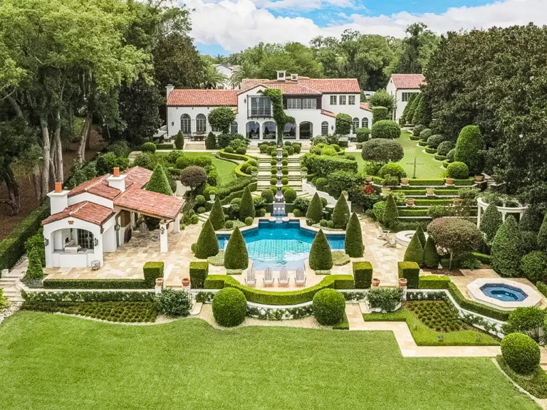 White House with red roof and green landscaping that surrounds a blue pool