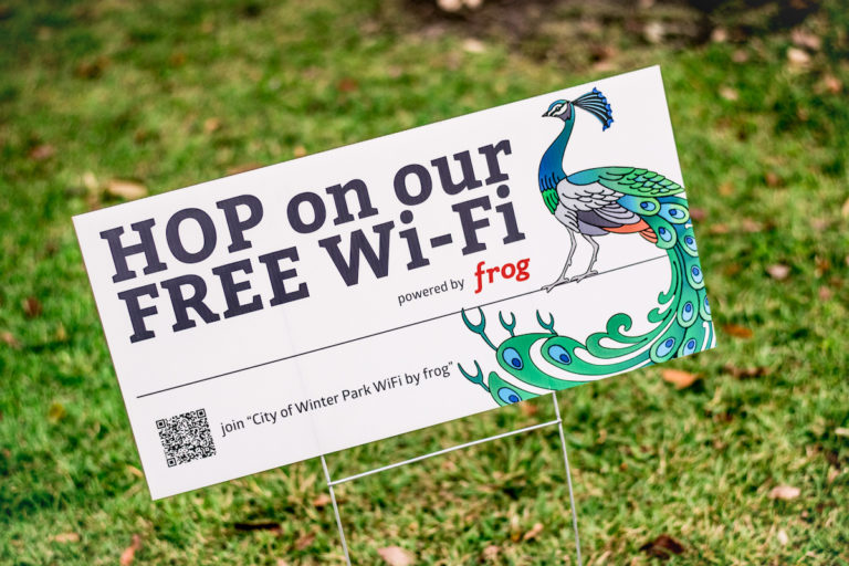 """A white sign that says """"Hop on our free Wi-Fi"""" has a blue peacock on it in green grass"""