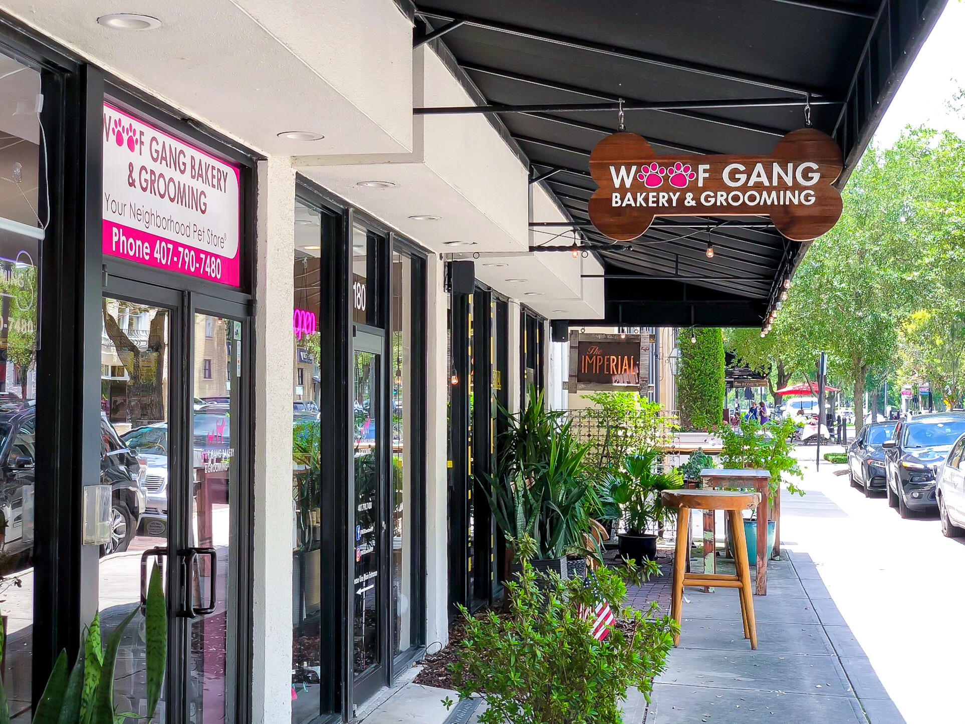 Building with black roof, white walls, green landscape, and a pink sign that says Woof Gang