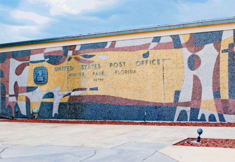 Wall with blue, red, and beige mural says United States Postal Service