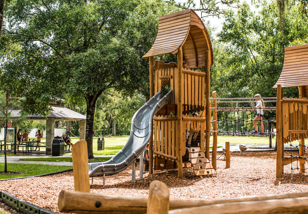 Image shows brown playground green trees