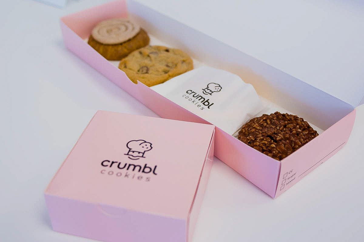 Pink box with four brown, beige, and chocolate cookies