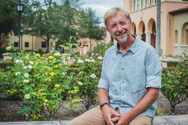 Artist Paul Day sits in front of the Rollins College rose garden.
